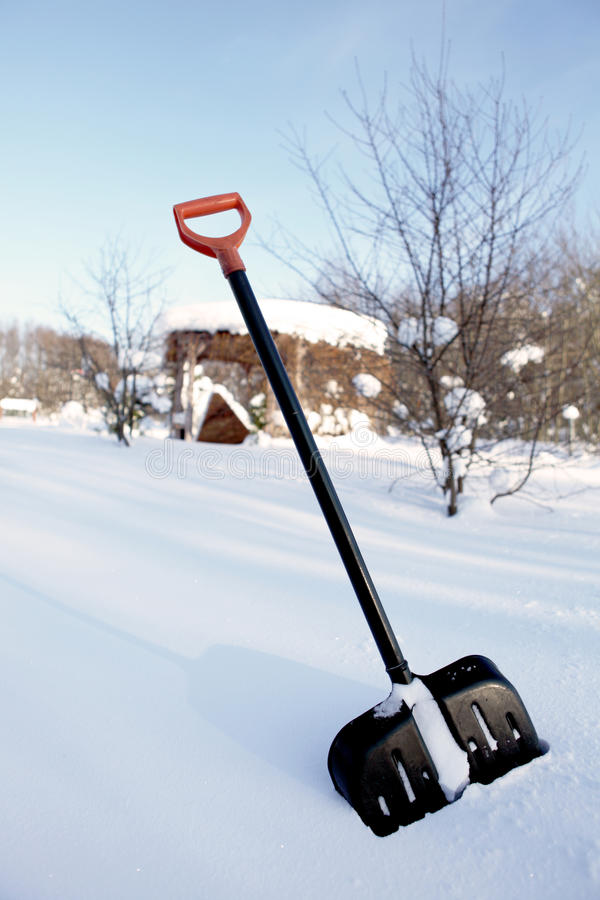Snow shovel with yellow handle stock photography