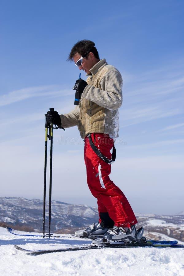Snow Skier with walkietalkie over blue Sky royalty free stock image