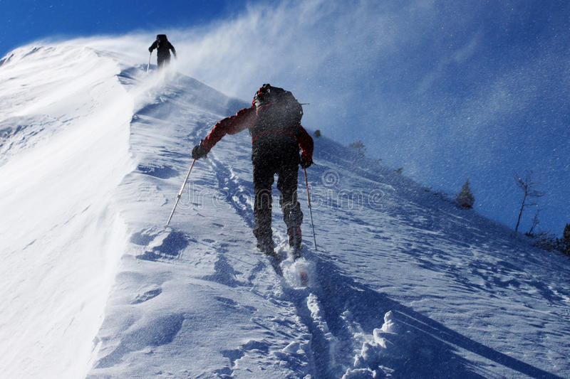 Snow storm. Two climbers ascending snow ridge in snow storm stock photography