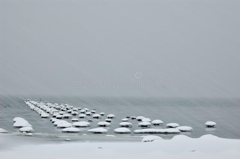 Snow storm on lake stock image
