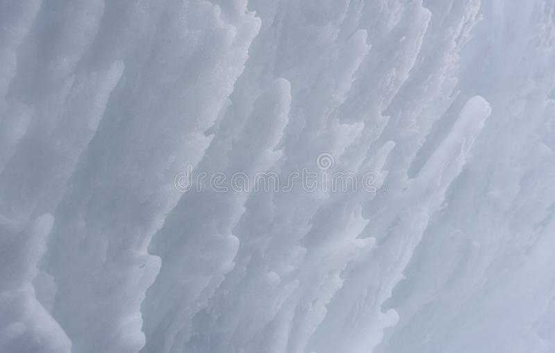 Snow wall close-up. White clean snow surface. Snow texture with waves of frozen snow. Wall of snow close-up stock photo
