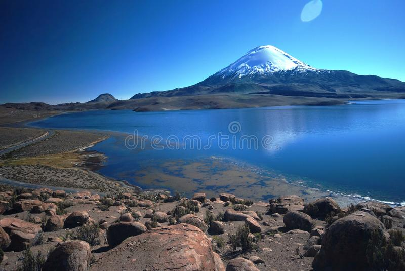 Snow volcano above blue lake royalty free stock photo