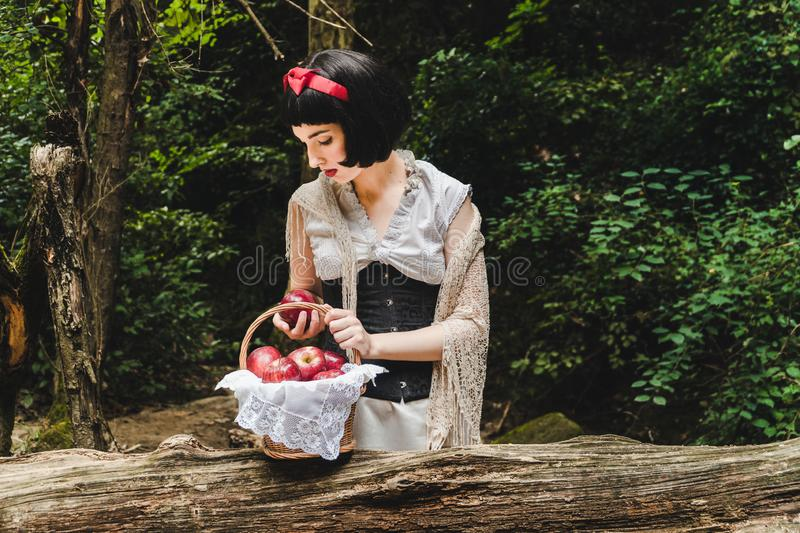 Snow White is in the forest, holding and looking to a red apple next to a basket full of apples royalty free stock photos