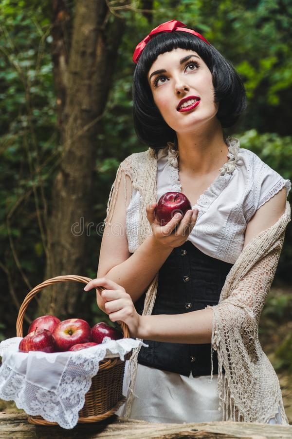 Snow White holds a red apple from a basket in her hand and looks up with a face full of dreams stock photos