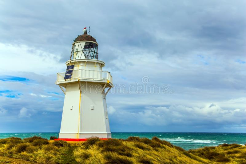 The snow-white lighthouse. The famous snow-white lighthouse of Waipapa is visible on the horizon. Scenic South Island on a cloudy windy day. Independent trip to royalty free stock photos