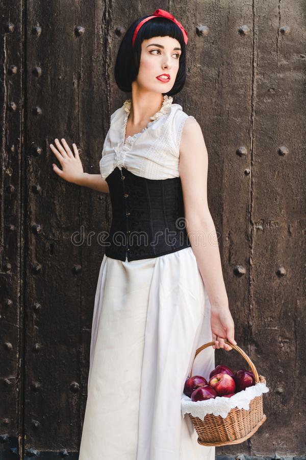 Snow White is looking to her left with a basket full of red apples royalty free stock photos