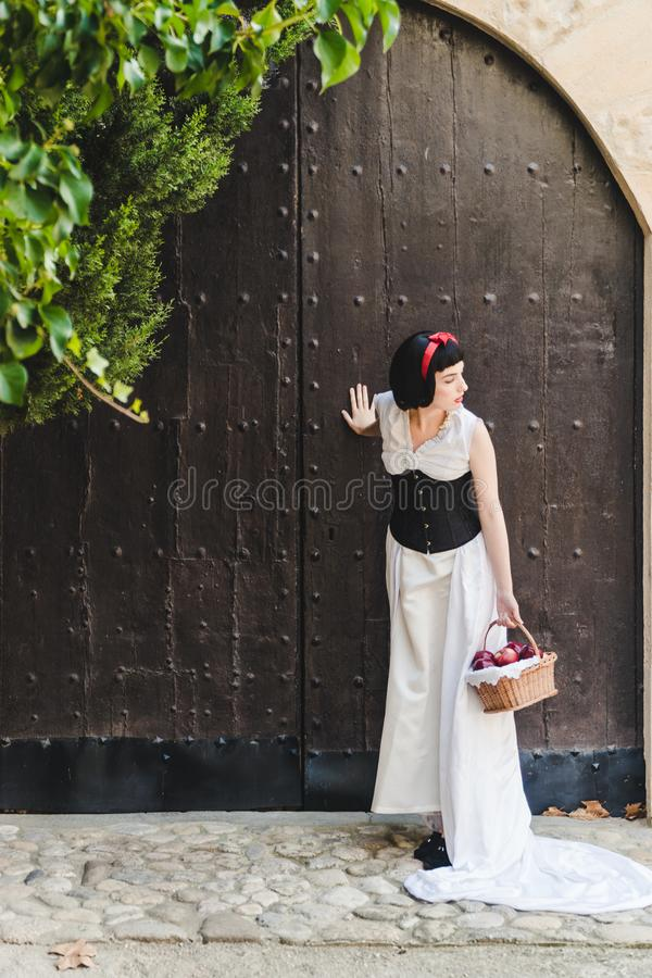 Snow White is looking to her left, with her hand on the door. She is carrying a basket of apples stock photo