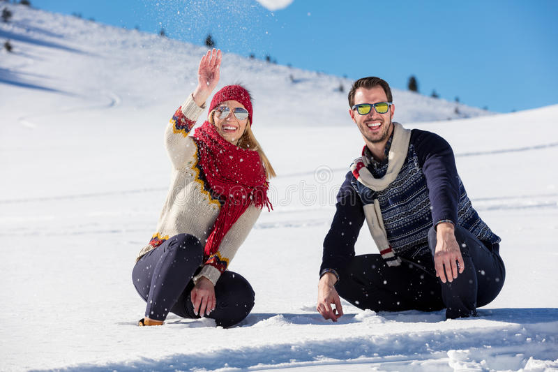 Snowball fight. Winter couple having fun playing in snow outdoors. Young joyful happy multi-racial couple. Snowball fight. Winter couple having fun playing in stock image