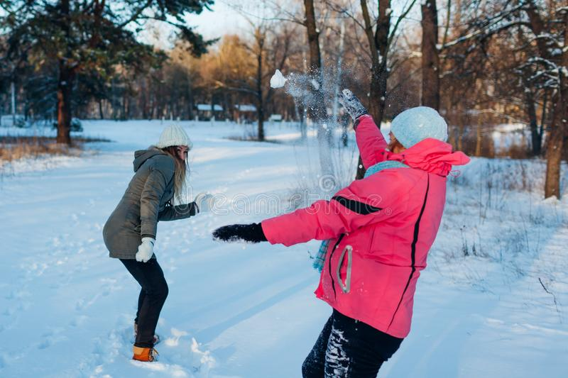 Snowballs playing in winter forest. Family mother and daughter having fun throwing snow outdoors stock photos