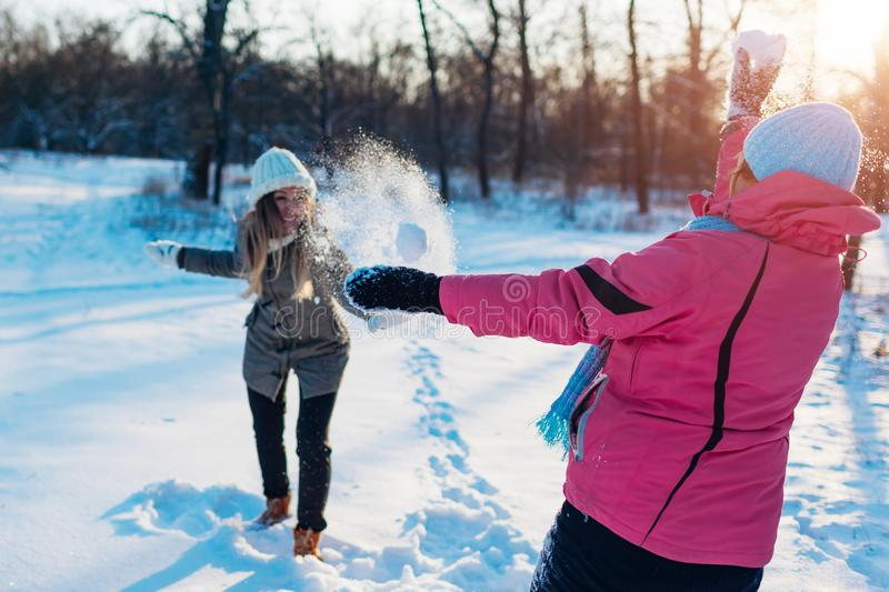 Snowballs playing in winter forest. Family mother and daughter having fun throwing snow outdoors royalty free stock photography