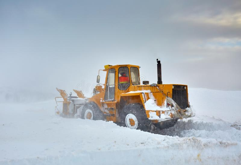 Snowblower at work in the mountains stock images