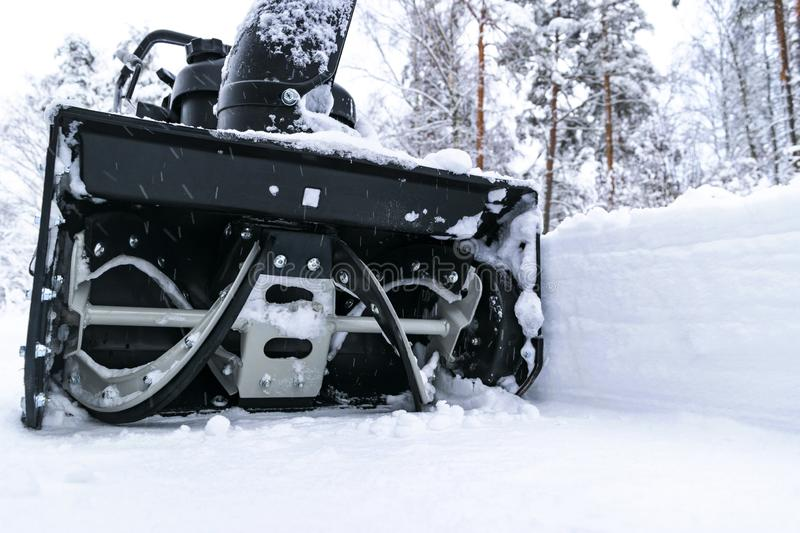 Snowblower at work on a winter day. Removing snow after blizzard snowfall. Clearing the ice. A snow blower is clearing a driveway stock photography