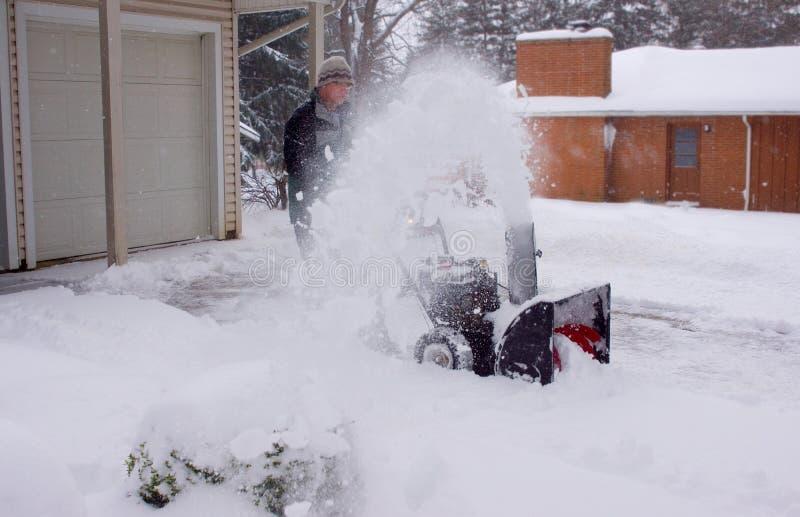 Snowblowerman som göras suddig av snö royaltyfri foto