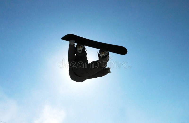 Snowboard. A snowboarder going big high above the half pipe royalty free stock photography