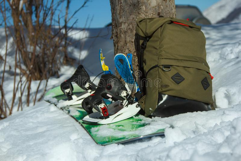 A snowboard and a backpack on the snow. Winter weekend royalty free stock photos