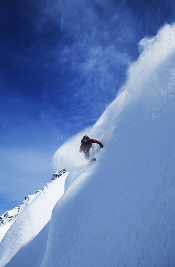 Snowboard del hombre en cuesta escarpada fotos de archivo