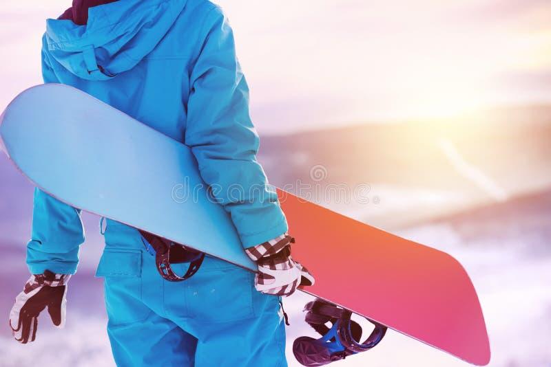Snowboard dello snowboard dello snowboarder della parte posteriore della donna del primo piano fotografie stock libere da diritti