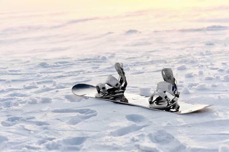 Snowboard en la nieve en la puesta del sol fotografía de archivo libre de regalías