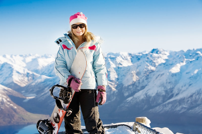 Snowboard girl. Woman holding snowboard with mountains in background