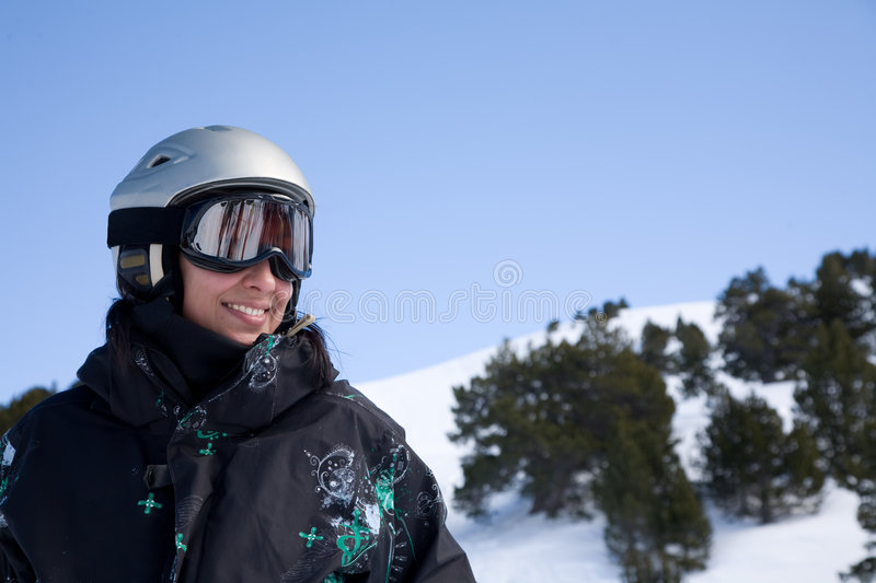 Snowboard girl. Pretty gorl in snowboard clothes in helmet over blue sky stock photos