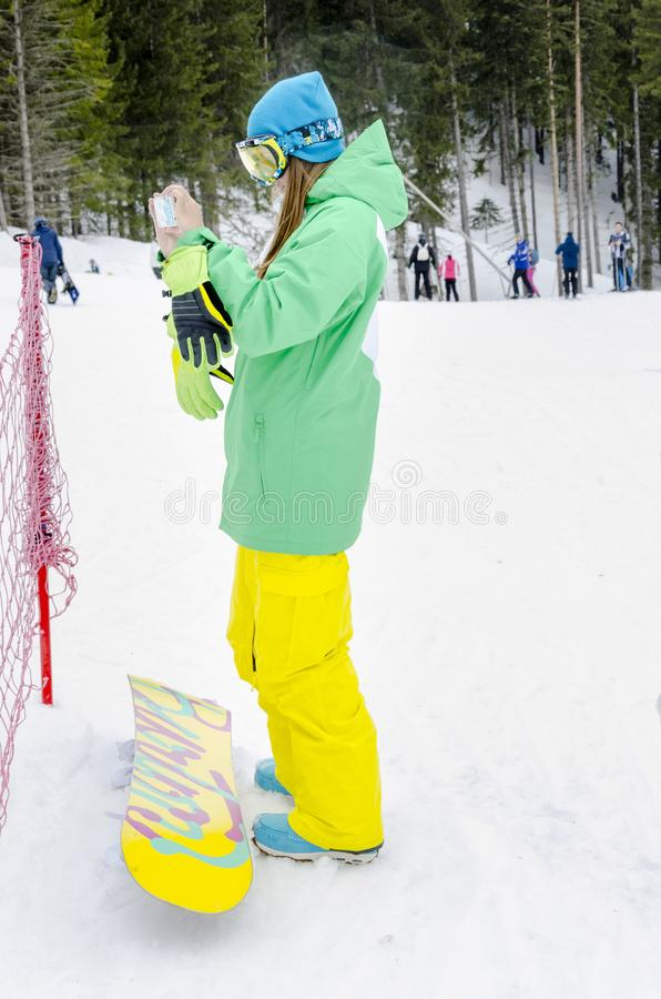Snowboard girl enjoying winter vacation making photos stock photography
