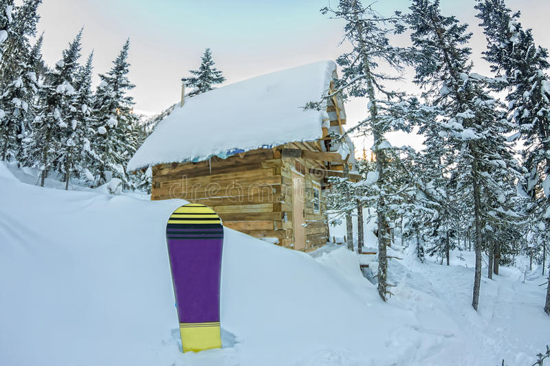 Snowboard at house chalets in winter forest with snow in mountains.  stock images