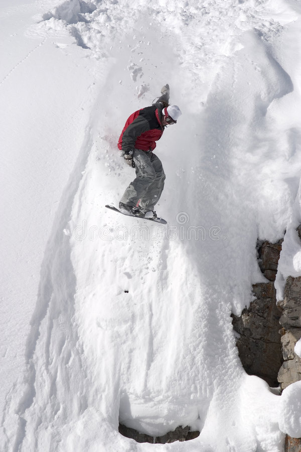 Snowboard jump from a cliff in the powder stock images