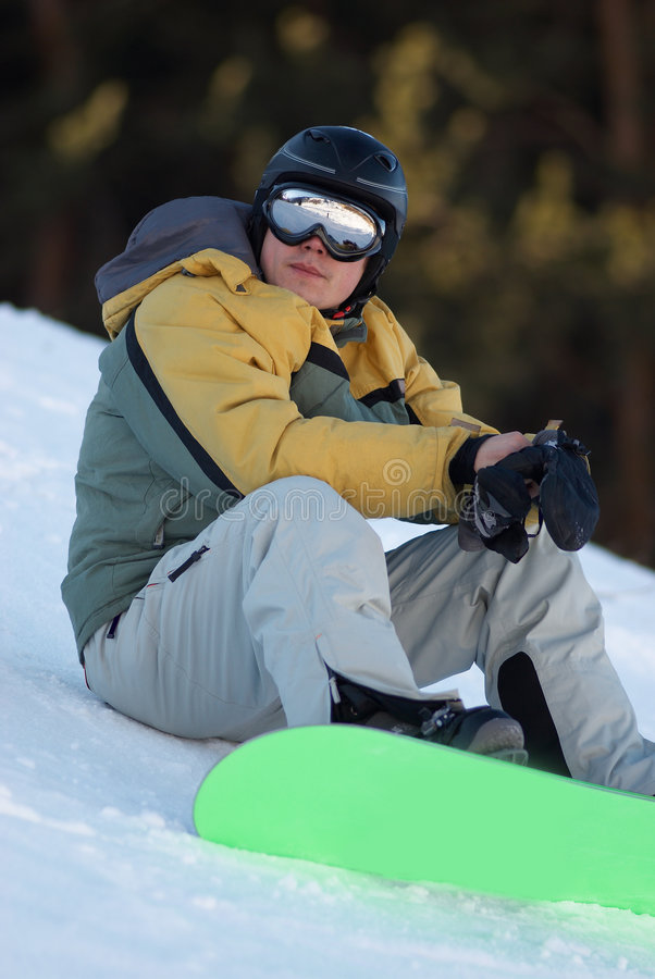 Snowboard man sits. On ski slope stock photo