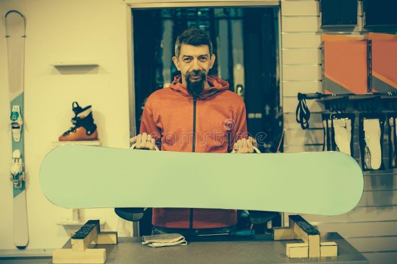 Snowboard remontowego sklepu pracownik przystosowywa oprawy obrazy stock