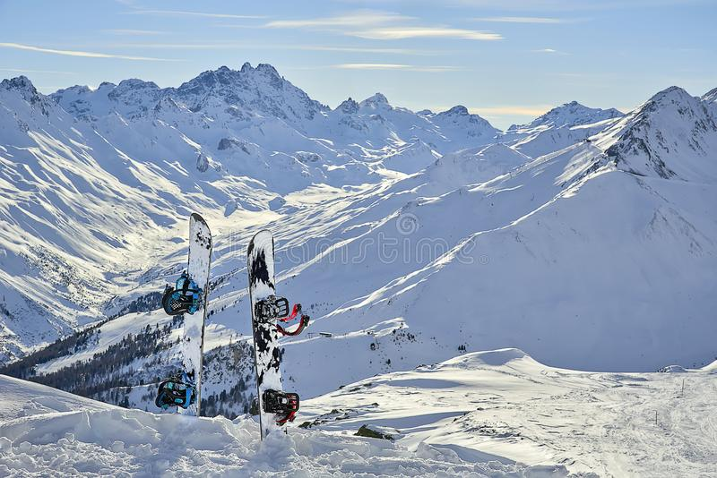 Snowboard in snow on off-piste slope at sun day between mountains on the background . Snowboard in snow on off-piste slope at sun day between mountains on the stock photography