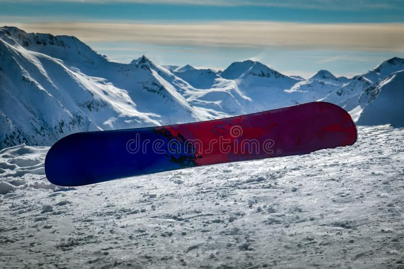 Snowboard in the snow surrounded by high snowy mountain peaks on beautiful sunny winter day. royalty free stock photos