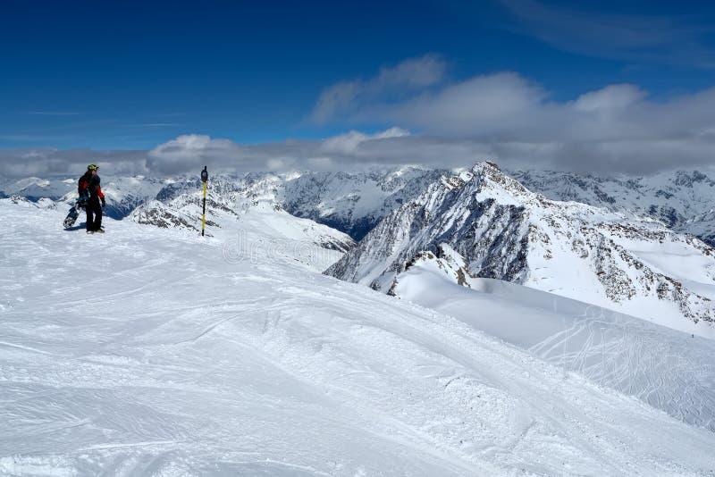 Snowboarder ?verst av ett berg i semesterorten av Solden arkivbilder