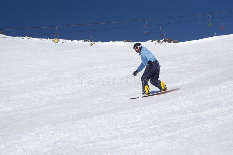 Snowboarder που οδηγά στη χιονώδη κλίση σκι στα υψηλά χειμερινά βουνά στην ηλιόλουστη ημέρα στοκ φωτογραφία