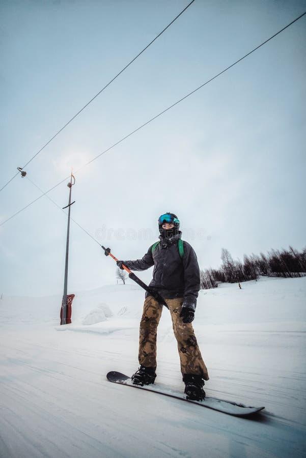 Snowboarder σε ένα μαύρο κράνος που οδηγά σε μια χιονώδη διαδρομή στοκ εικόνες