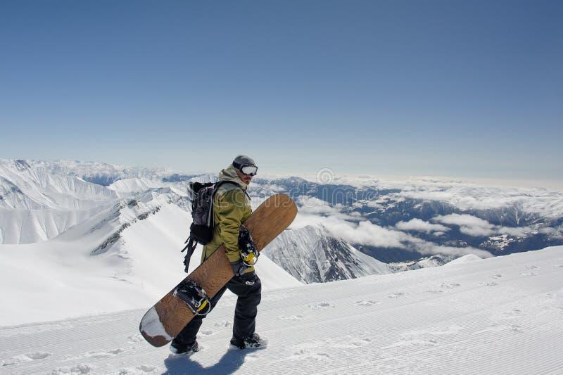 Snowboarder взгляда со стороны manful идя со сноубордом в m стоковые фотографии rf