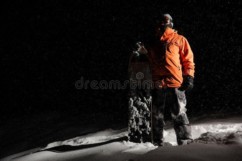 Snowboarder в оранжевом sportswear и маска стоя с доской стоковая фотография