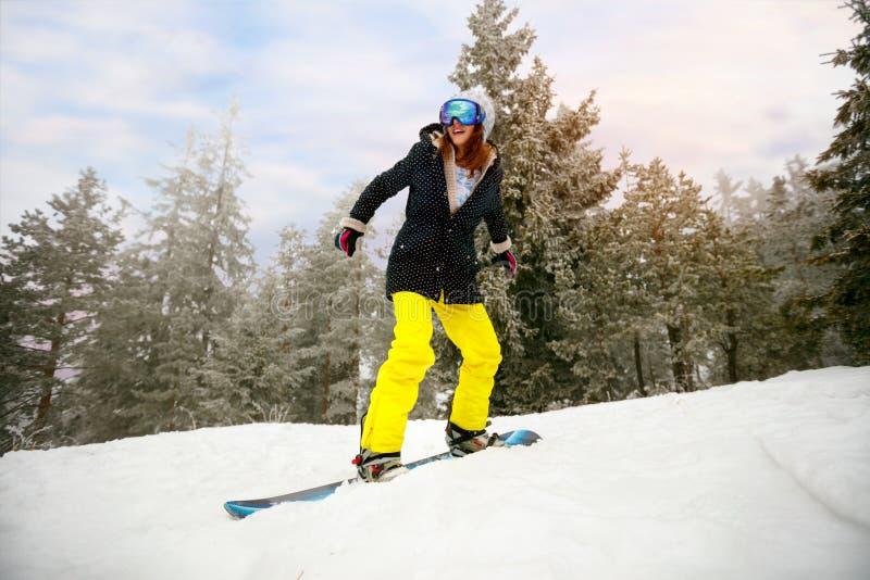 Snowboarder девушки в скачке на лыжном курорте в зиме e горы стоковое изображение