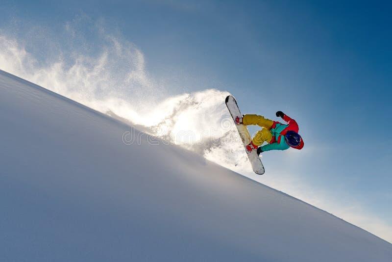 Snowboarder девушки скача переднее сальто выходя волна снега стоковые фотографии rf