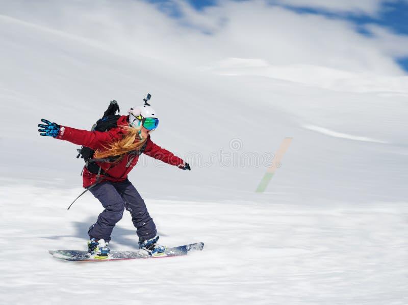Snowboarder девушки идет быстро вниз с наклона и кричит стоковое фото rf