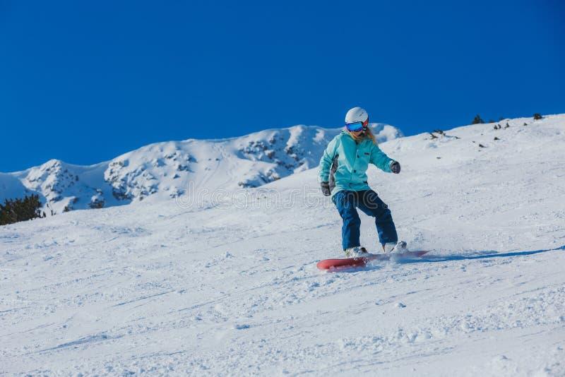Snowboarder женщины в горах стоковая фотография rf