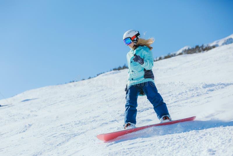 Snowboarder женщины в горах стоковая фотография