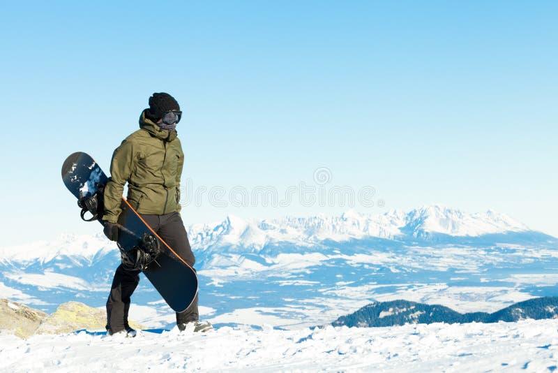 Snowboarder идя вверху гора с его сноубордом в руке стоковые изображения rf