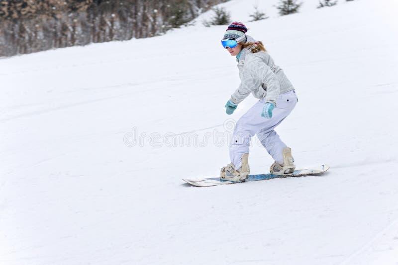 Snowboarder молодой женщины в движении на сноуборде в горах стоковое фото rf
