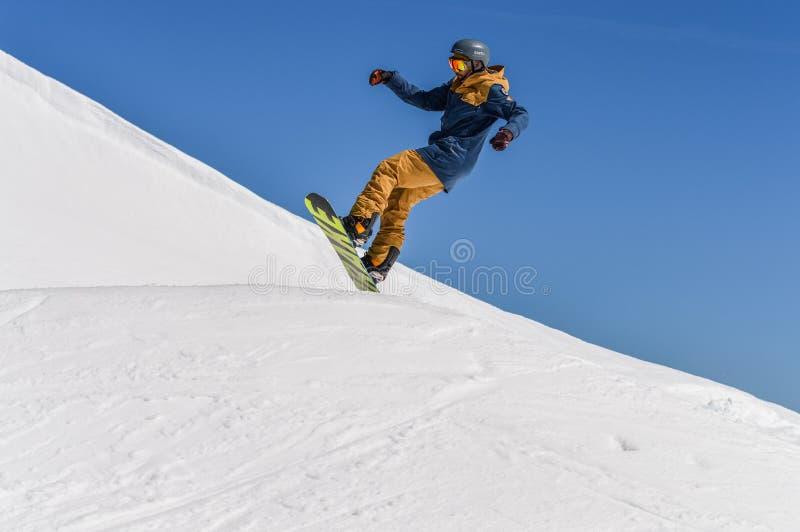 Snowboarder наслаждаясь бегами и скачки на ` s весны продолжают снег стоковое фото