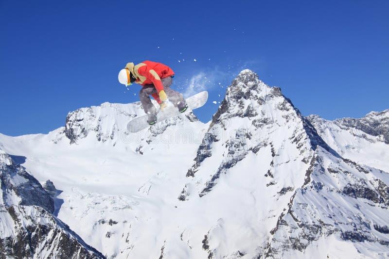 Snowboarder на горах, весьма спорт летания стоковое изображение