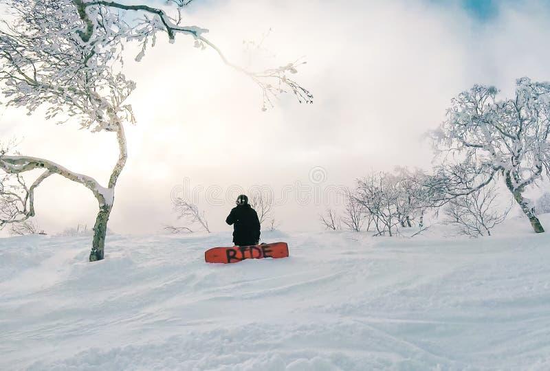 Snowboarder от за вставать на колени на снежной горе стоковое фото rf