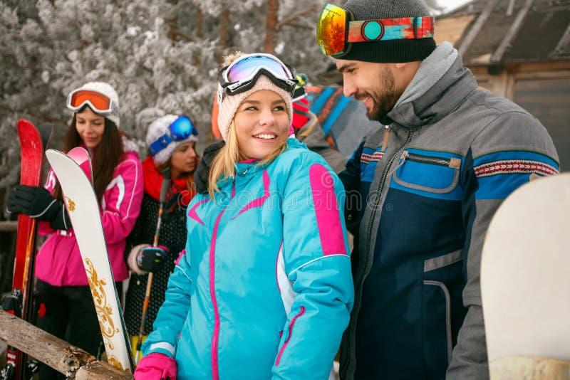 Snowboarder пар проводя совместно зимние отдыхи на горе стоковое фото