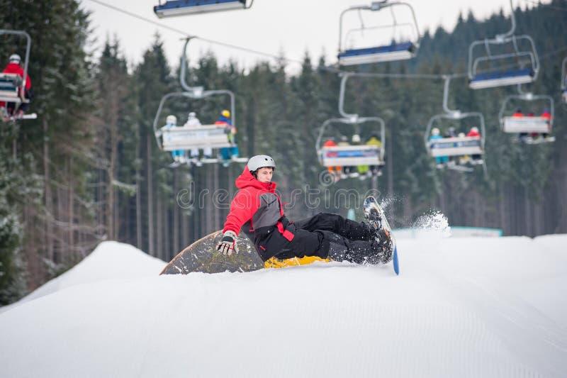 Snowboarder падает на наклоны во время скакать стоковое фото rf