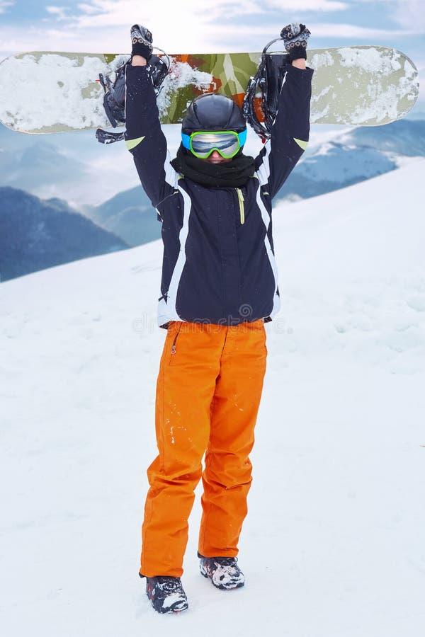 Snowboarder против панорамного сноуборда владением предпосылки гор зимы na górze холма стоковые изображения