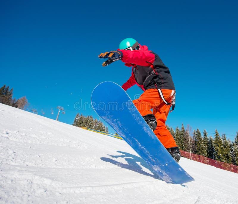 Snowboarder скача в воздух пока едущ на наклоне на лыжном курорте зимы в горах стоковые фото